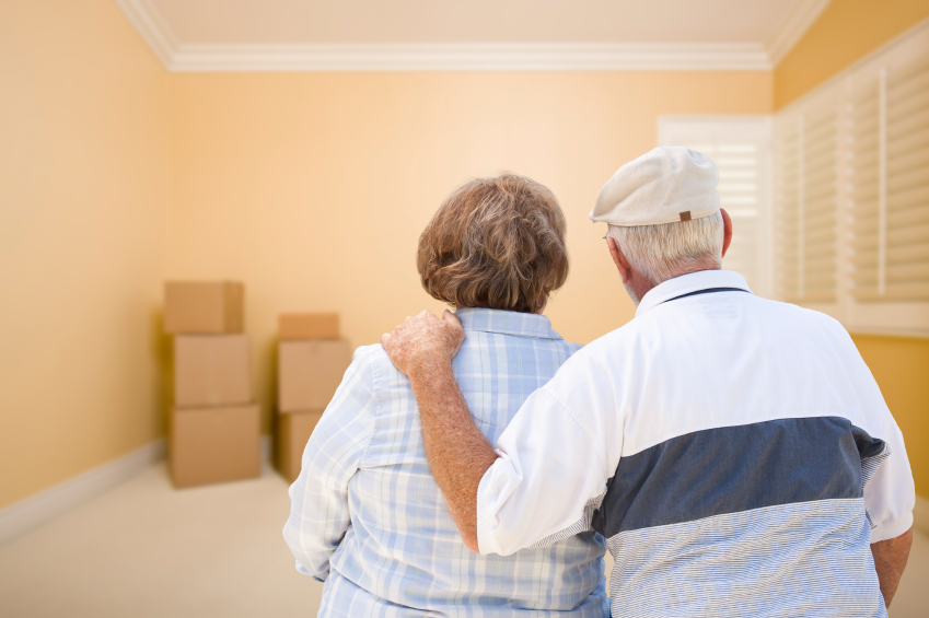 Hugging Senior Couple Looking at Moving Boxes